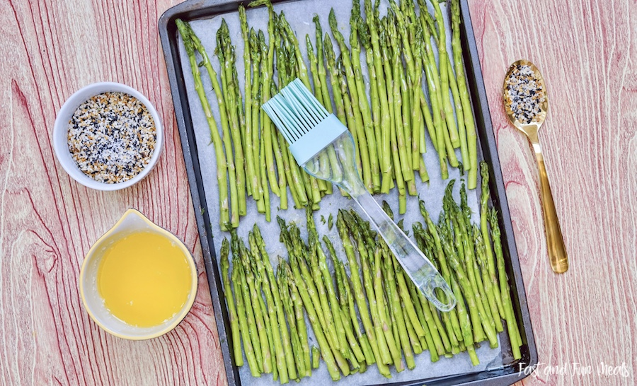 Coating the asparagus sheet pan with butter.