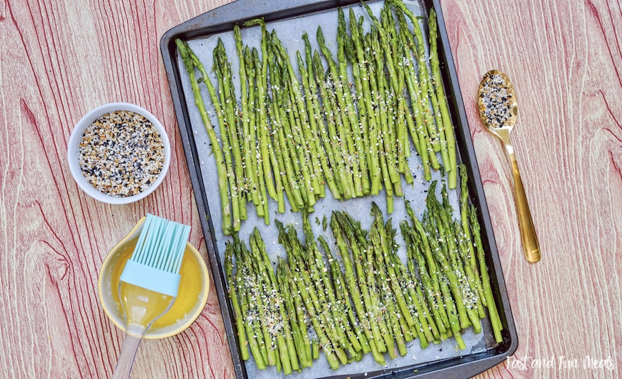 Brushing the sheet pan asparagus with butter.